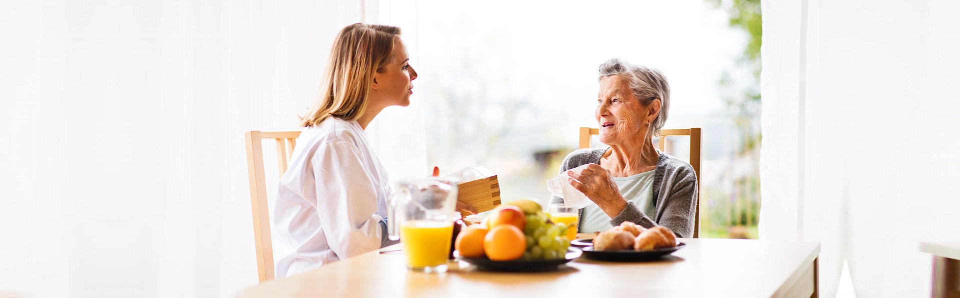 caregiver and old woman having a conversation while the old woman having her meal