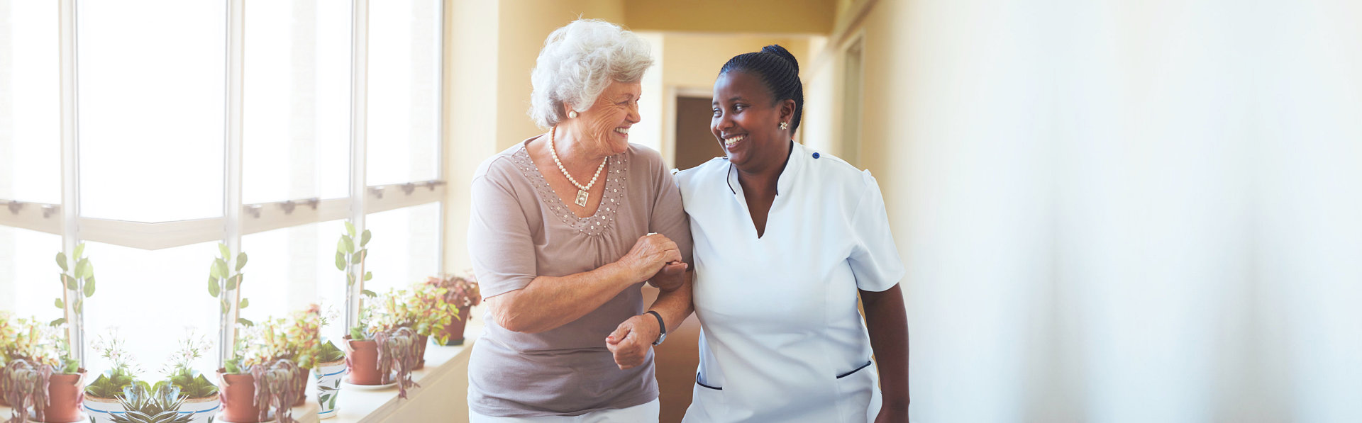 caregiver and old woman happily talking