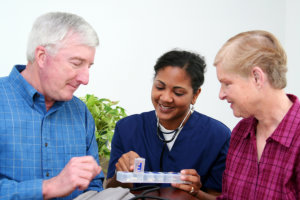 caregiver assists the elderly couple's medication