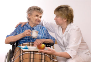 caregiver giving food to the elderly woman
