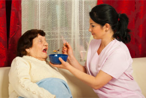 caregiver feeding the elderly woman